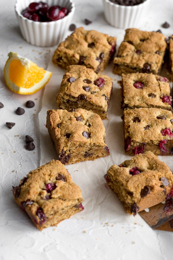 Side view of fresh cranberry chocolate chip cookies cut into bars and arranged on parchment paper.