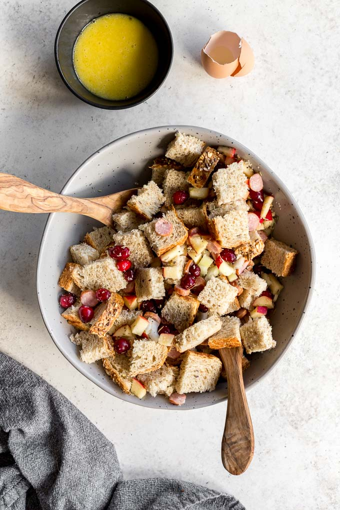 Sausage stuffing ingredients tossed together with wooden spoons.