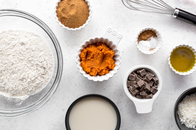 Ingredients to make Healthy Pumpkin Bread arranged on a white surface.