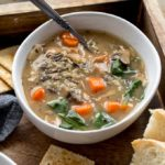 Instant Pot Chicken and Wild Rice Soup in a white bowl with bread and crackers off to the side.