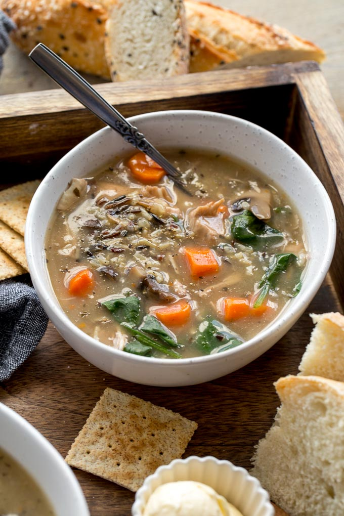 Chicken and Wild Rice Soup in a white bowl with bread and crackers off to the side.