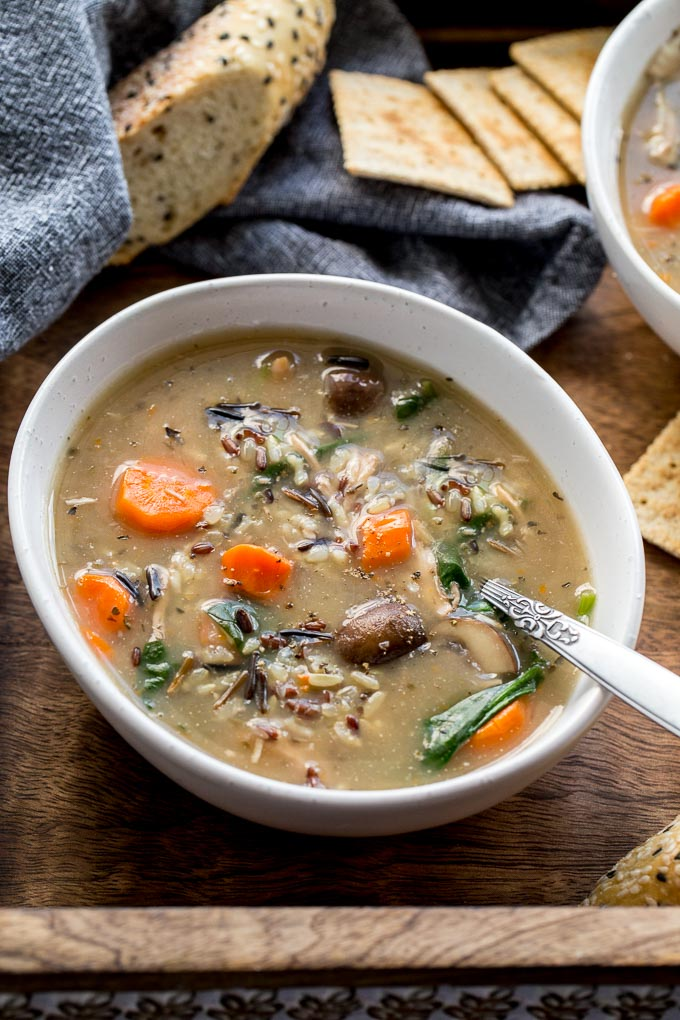 Up-close view of Instant Pot Chicken and Wild Rice Soup in a white bowl on a wooden tray.