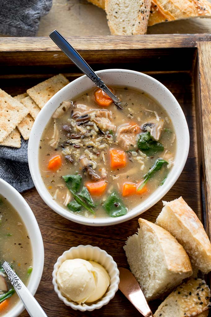 Overhead view of a bowl of Chicken and Wild Rice Soup on a wooden tray with bread.
