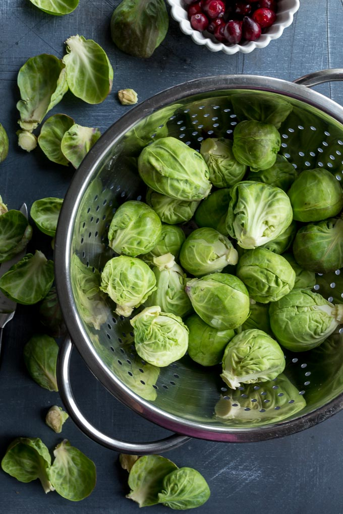 Overhead view of raw Brussels sprouts trimmed and washed in a colander.