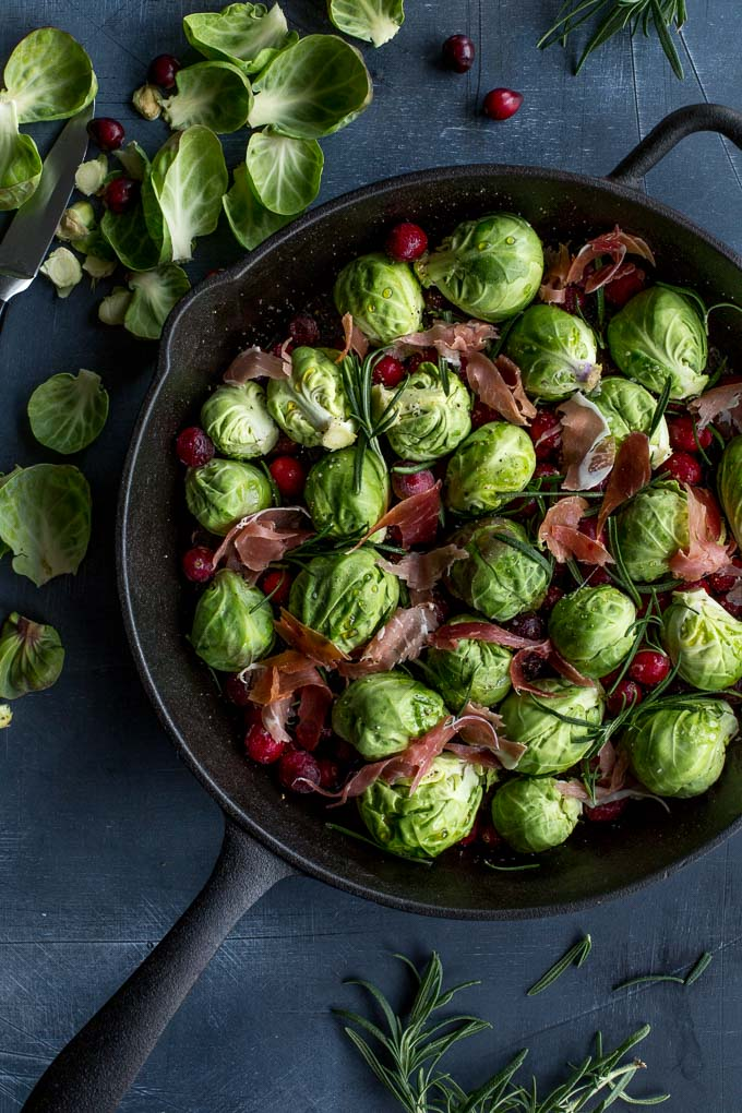 Overhead view of raw Brussels sprouts and other ingredients arranged in a cast iron skillet and ready for roasting.