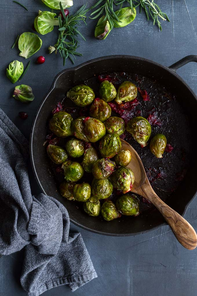 Overhead view of Roasted Brussels Sprouts with cranberries and prosciutto in a cast iron skillet.