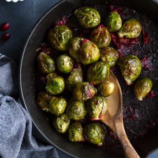 Overhead view of Roasted Brussels Sprouts in a cast iron skillet with a wooden spoon scooping some out.