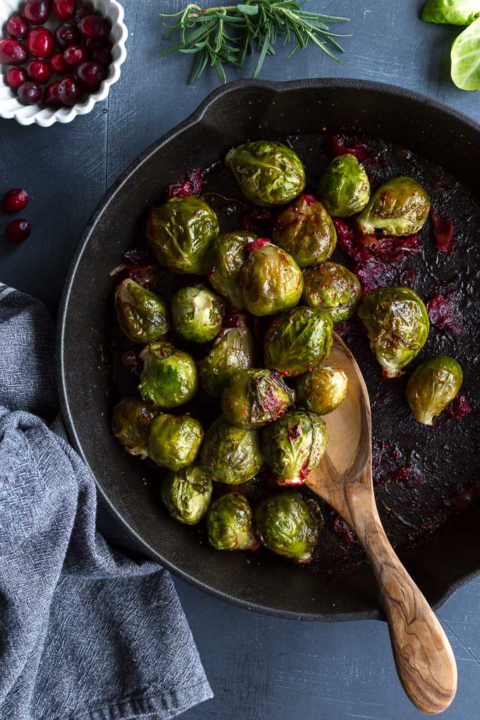 Overhead view of Roasted Brussels Sprouts in a cast iron skillet with cranberries off to the side.