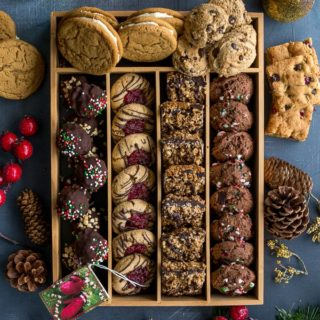 Overhead view of Christmas cookies arranged in a box on a dark surface.
