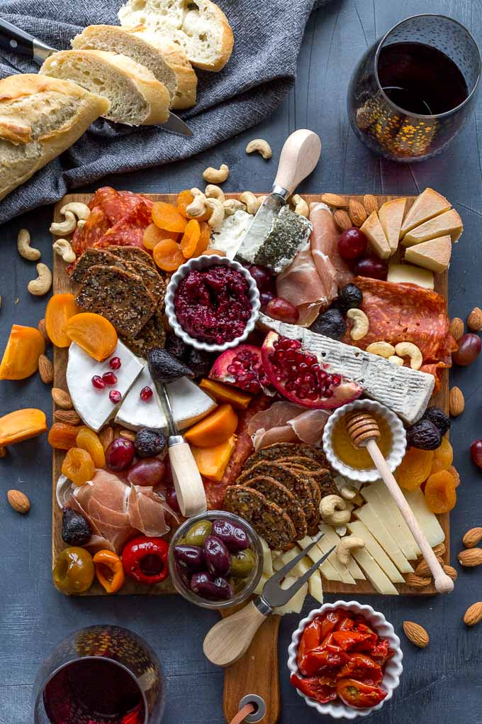 Overhead view of a fully assembled cheese board with bread and wine off to the side.
