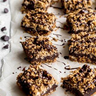 Chocolate Chai Spice Crumble Bars topped with chocolate and arranged on parchment paper.