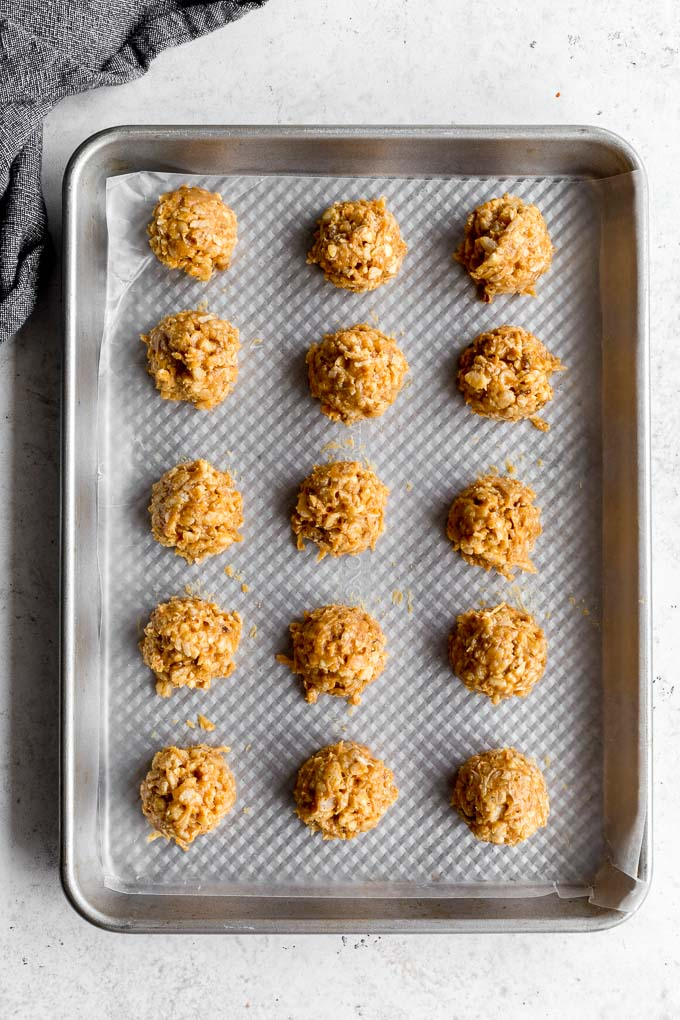 Crispy peanut butter balls arranged on a baking sheet and ready for dipping in chocolate.