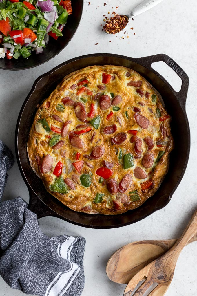 Overhead view of sausage frittata in a cast iron skillet next to a bowl of salad.