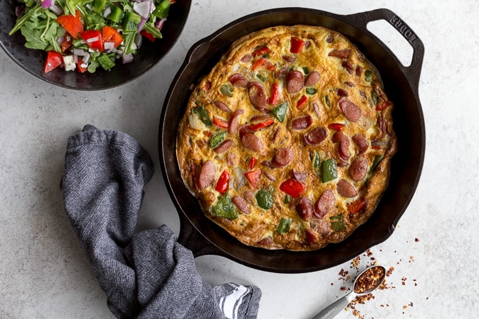 Sausage frittata with peppers and onions in a cast iron skillet with a cloth around the handle.