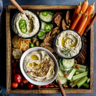 White bean dips arranged in a wooden tray with crackers and veggies for dipping.