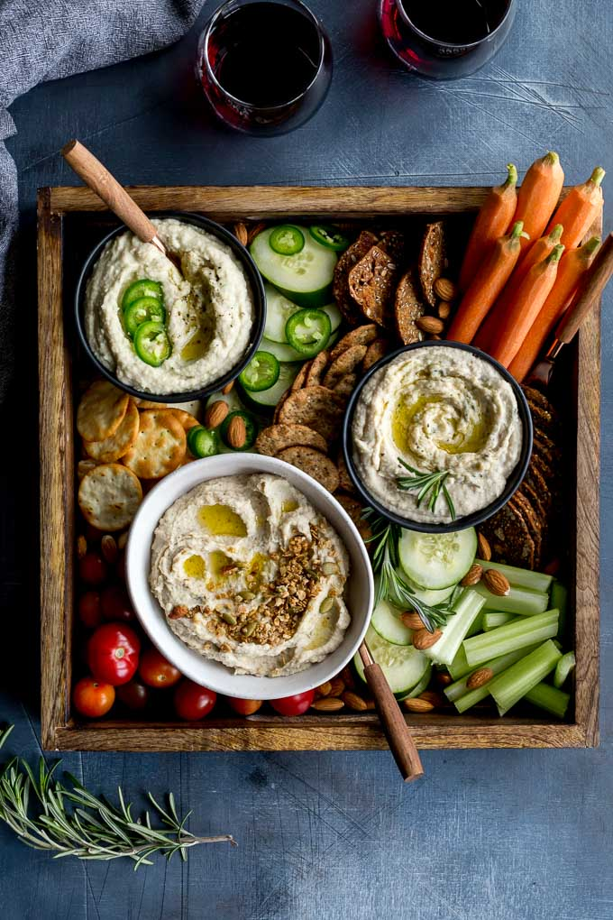 Overhead view of three white bean dips arranged in a tray with crackers and veggies.