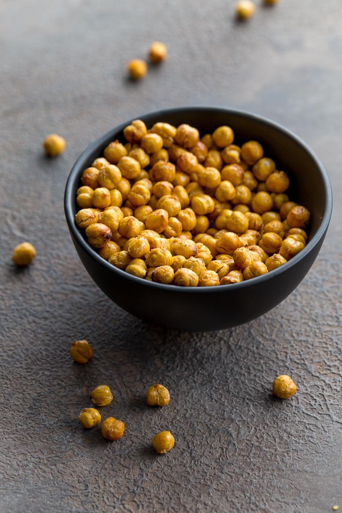 Up-close view of air fryer chickpeas in a black bowl with a few chickpeas scattered around.