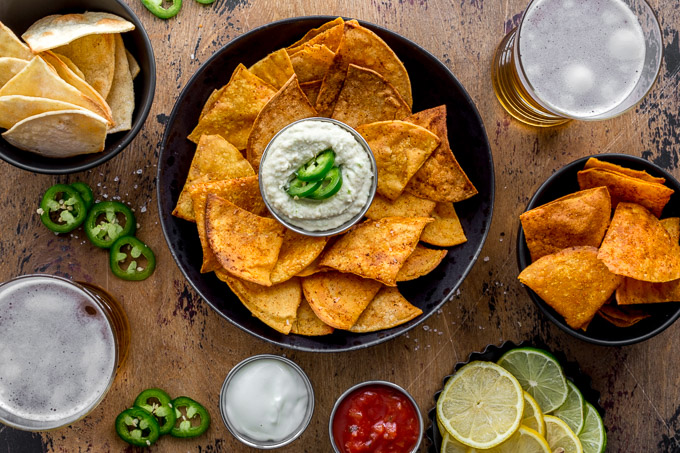 Overhead view of air fryer chips arranged in black bowls with dips and beer surrounding them.