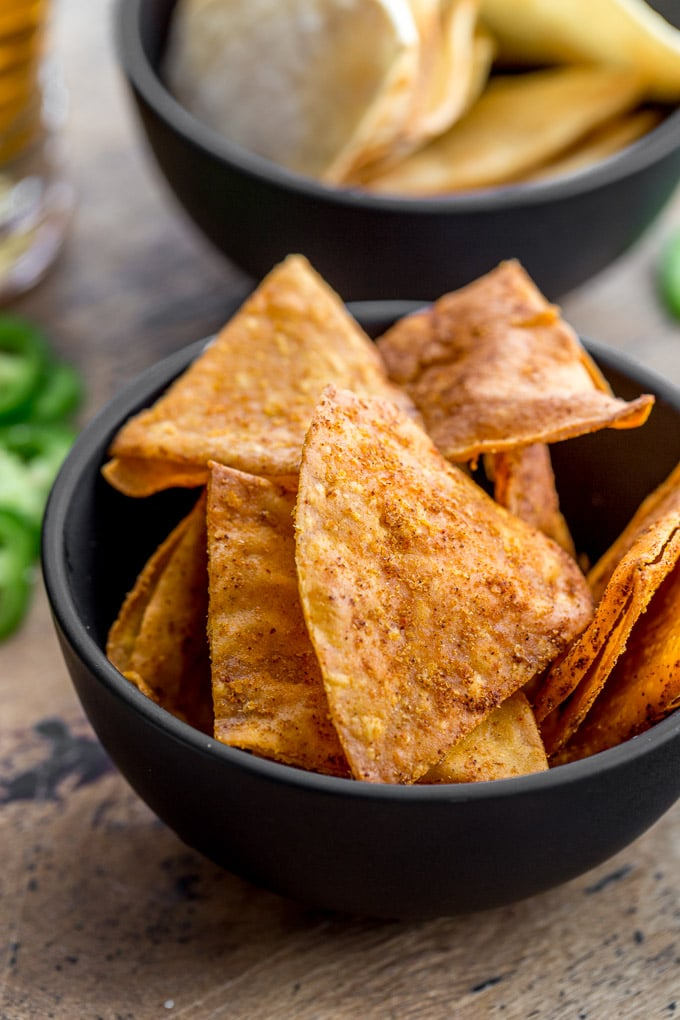 Up-close view of zesty cheese tortilla chips in a small black bowl.
