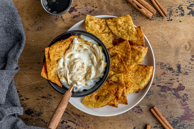 Maple cinnamon tortilla chips arranged on a plate with a bowl of yogurt.