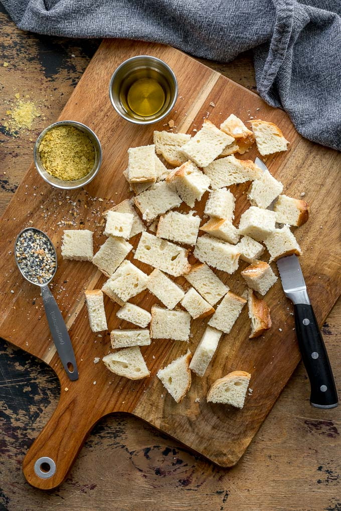 Cubes of bread on a wooden cutting board.