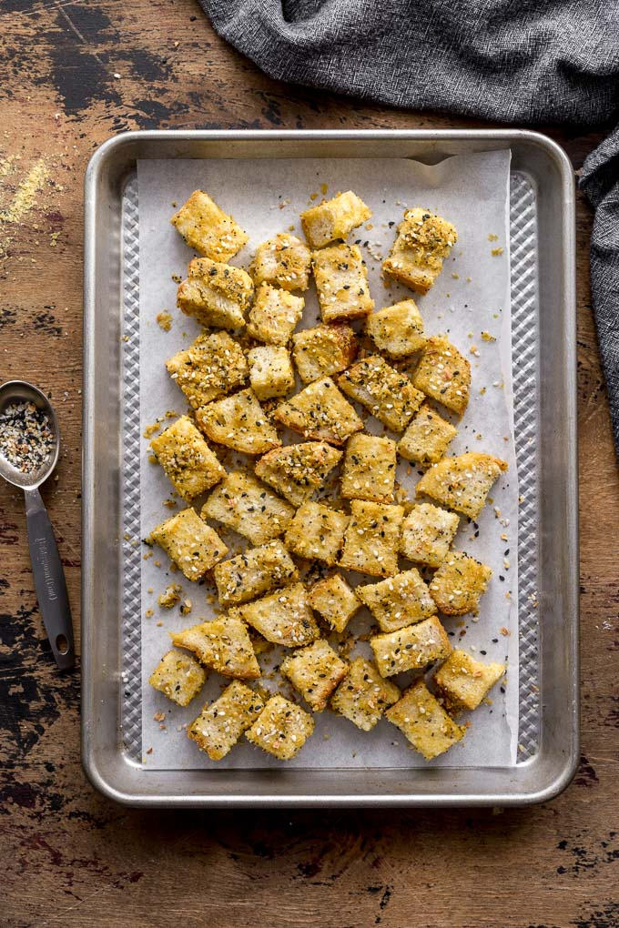 Overhead view of bread cubes arranged on a baking sheet and ready for the oven.