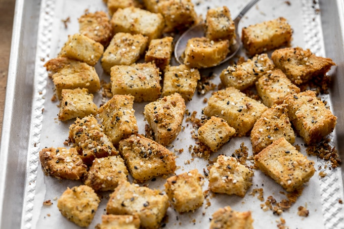 Up-close view of Cheesy Everything Bagel Croutons on a baking sheet.