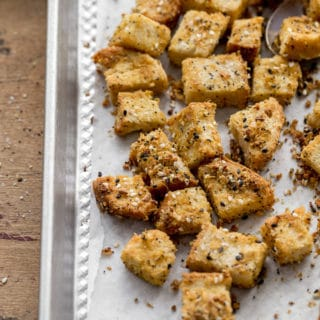 Cheesy Everything Bagel Croutons cooling on a baking sheet.