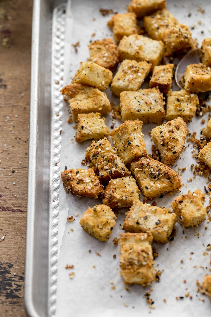 Everything Bagel Croutons cooling on a baking sheet.