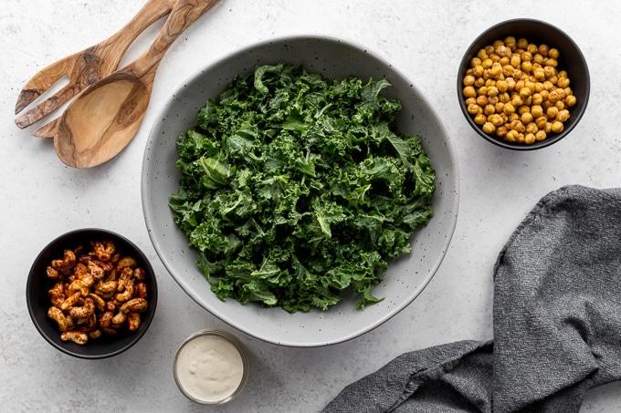 Ingredients to make vegan caesar salad arranged individually on a white surface.
