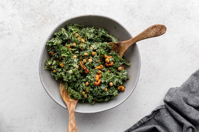 Kale salad mixed together with dressing and toppings using large wooden spoons.