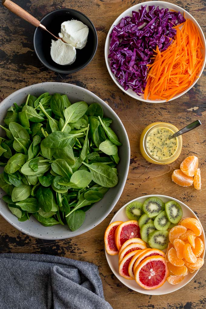 Ingredients to make Winter Salad arranged on a wooden surface.