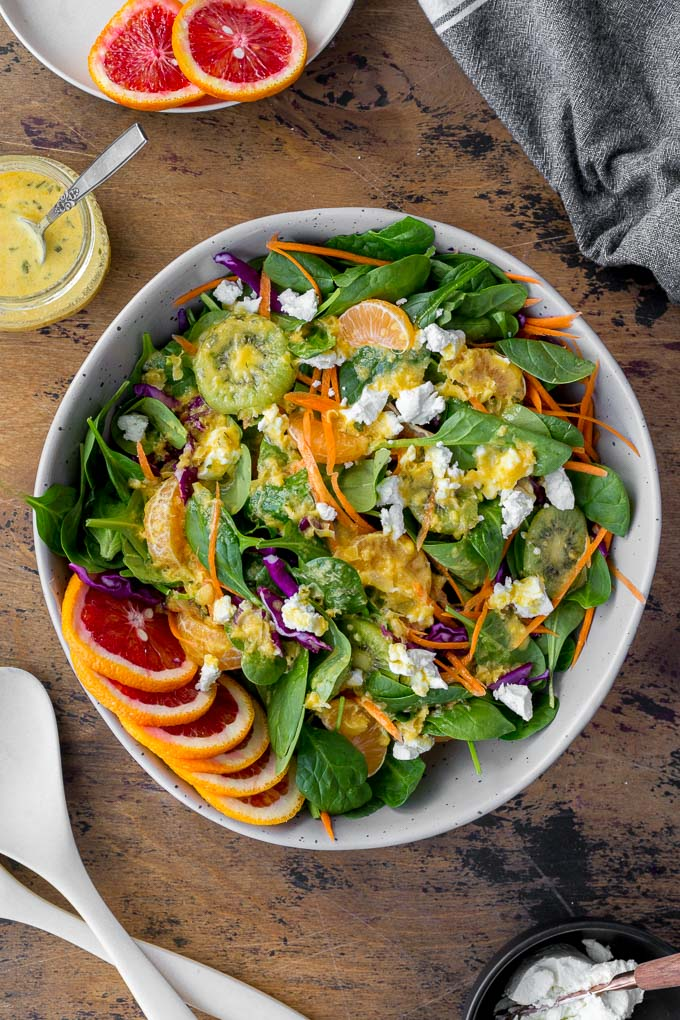 Overhead view of Winter Salad in a large grey bowl and topped with Citrus Honey Dressing.