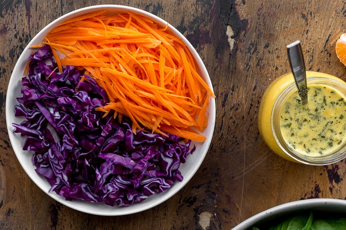 Shredded carrot and red cabbage on a plate next to a jar of dressing.