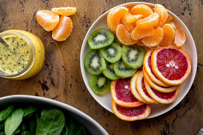 Sliced kiwis and oranges arranged on a plate.