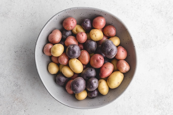 A large bowl of raw and whole tri-colour baby potatoes.