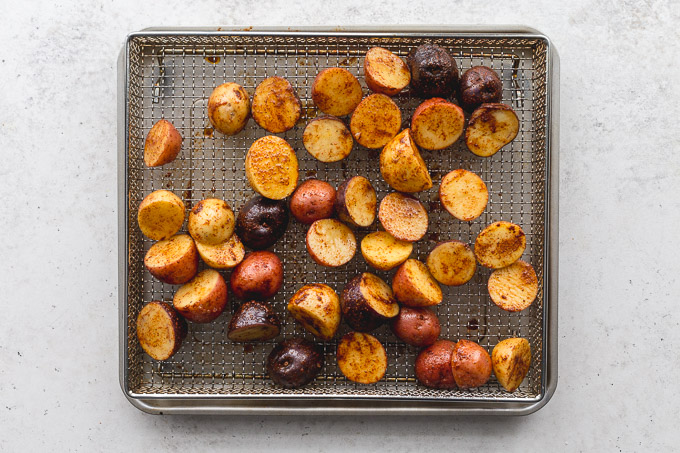 Seasoned baby potatoes cut in half and arranged in an air fryer basket.