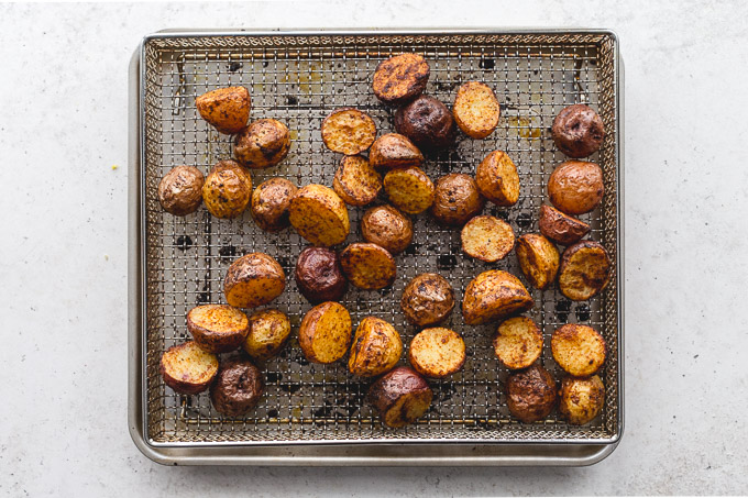 Baby potatoes air fried and resting in an air fryer basket.