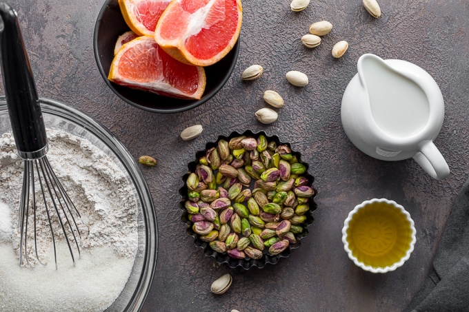 Ingredients to make grapefruit pistachio cake arranged on a dark surface.