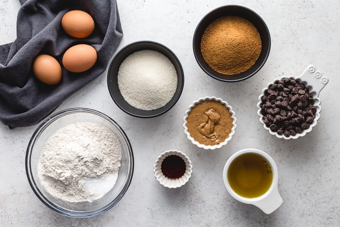 Ingredients to make almond butter brownies arranged individually on a white surface.