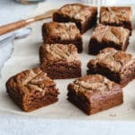 Salted Almond Butter Brownies cut into squares and placed on a sheet of parchment paper.