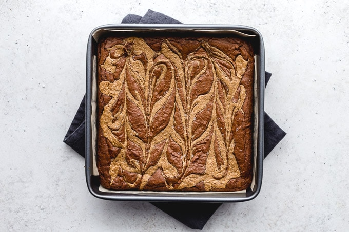 Salted almond butter brownies cooling in a square pan.
