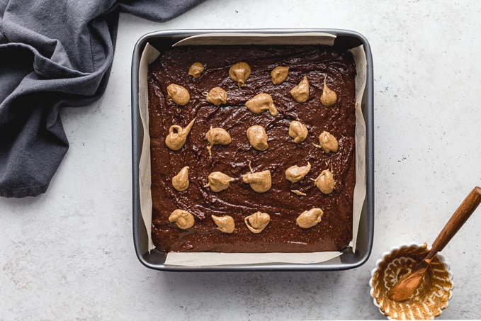 Brownie batter in a pan with dollops of almond butter on top.