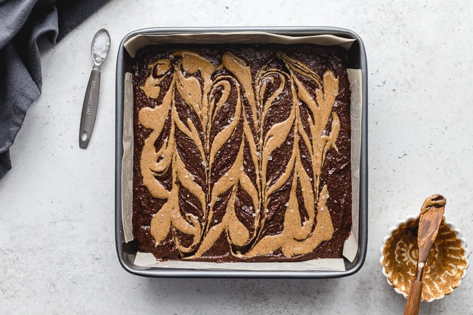 Brownie batter in a pan with swirls of almond butter on top.