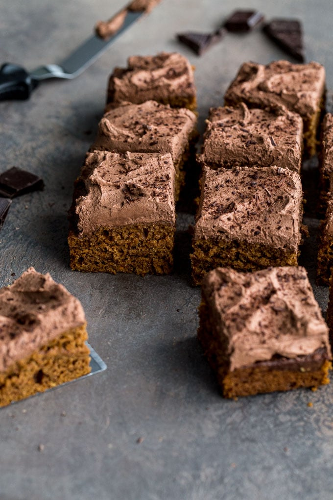 Side view of sweet potato cake with chocolate coconut frosting cut into squares.