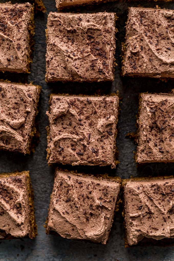 Up-close view of frosted sweet potato cake cut into squares.