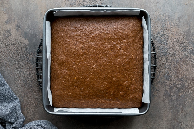 Sweet potato cake in a square pan and cooling on a wire rack.