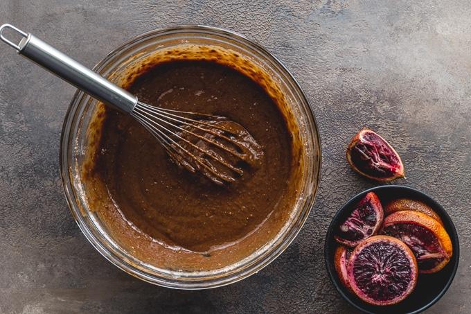 Blood orange cake batter in a glass bowl.