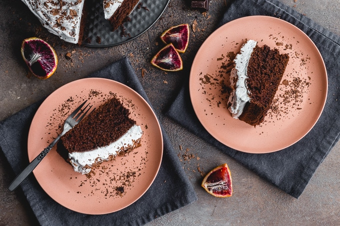 Two slices of chocolate cake on pink plates.