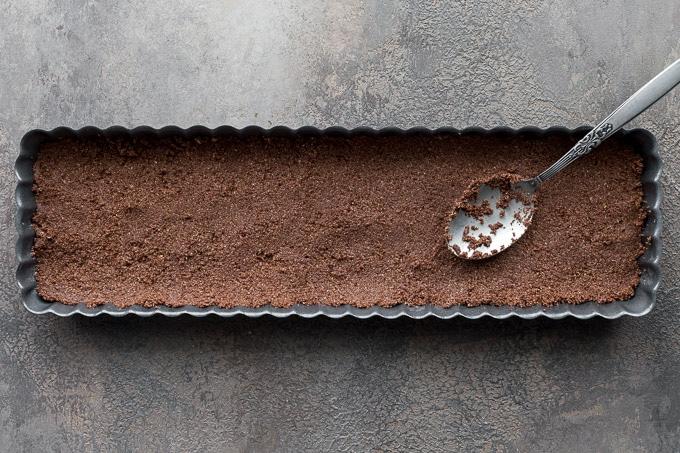 Chocolate crust being pressed into a rectangular tart pan.